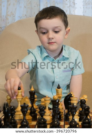 Boy playing chess. Man thinks and makes the next move. - stock photo