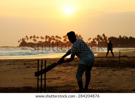 Boy playing cricket at sunset on tropical beach in Sri Lanka - stock photo