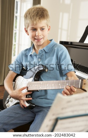 Boy playing electric guitar at home - stock photo