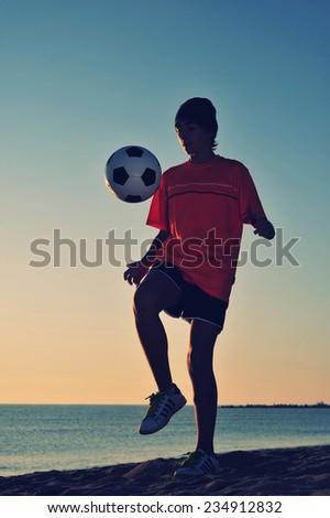 Boy playing football on beach - stock photo