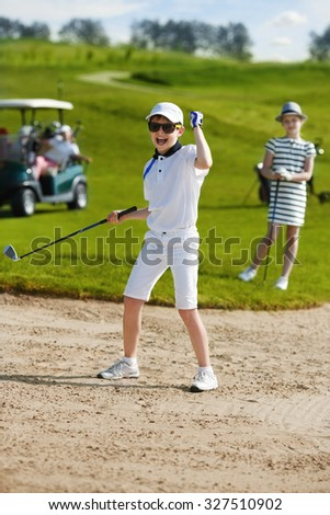 Boy playing golf and enjoing on the successful hit - stock photo