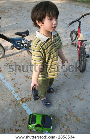 Boy playing green remote control car at the children playground - stock photo
