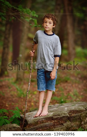 boy playing in a summer forest looking at the camera - stock photo