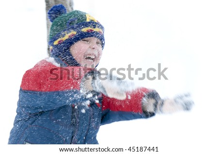 Boy playing in the snow with snow on his face - stock photo