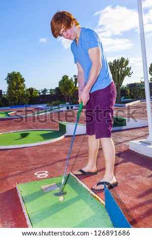 boy playing mini golf in the course - stock photo