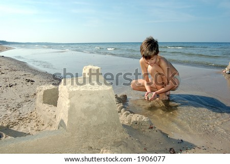 Boy playing on the beach - stock photo
