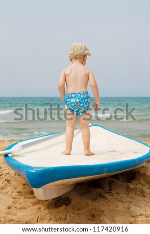 Boy playing on the golden beach - stock photo
