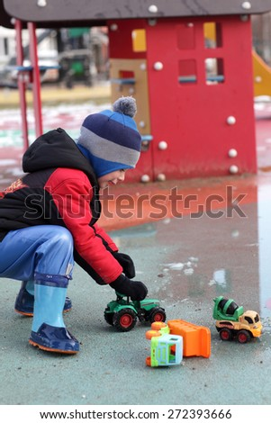 Boy playing on the playground in spring - stock photo