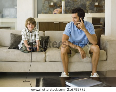 Boy playing playstation, father on the phone. - stock photo