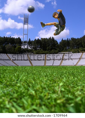 Boy playing soccer in a green grass field - stock photo