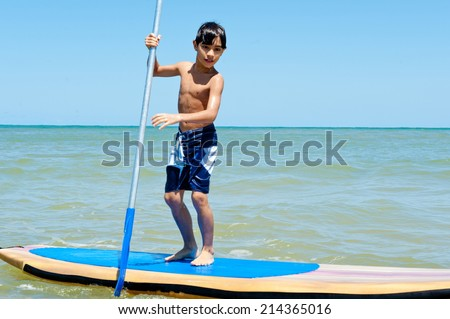 Boy playing Stand Up paddle board - stock photo