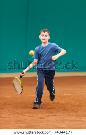 Boy playing tennis on a dross court, some motion blur on the arm as he hits the ball - stock photo