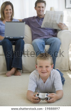 Boy playing video game while parents watch - stock photo