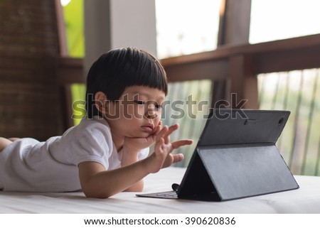 Boy playing with digital tablet.