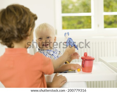 Boy playing with little brother - stock photo