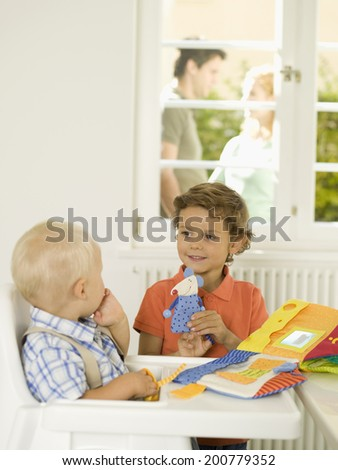 Boy playing with little brother, couple in background - stock photo