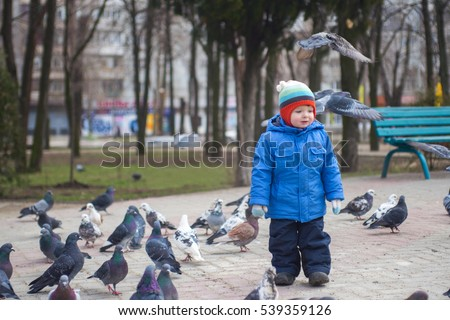Boy playing with pigeons doves birds in city park