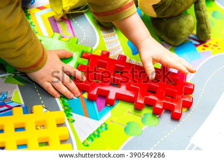 Boy playing with plastic blocks in home. Caucasian child build something with blocks - stock photo