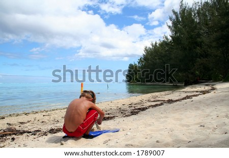 boy playing with sand on the beach, with snorkeling gear on - stock photo
