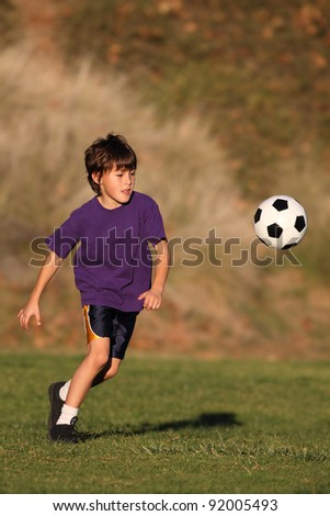 Boy playing with soccer ball in early evening sunlight - stock photo