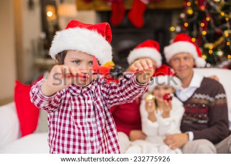 Boy playing with toy airplane in front of his family on couch at home in the living room - stock photo