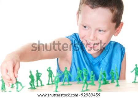 Boy playing with toy soldiers - stock photo