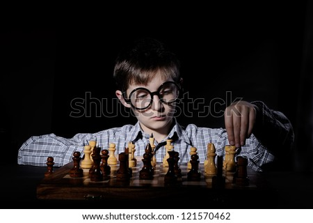 Boy plays chess - stock photo