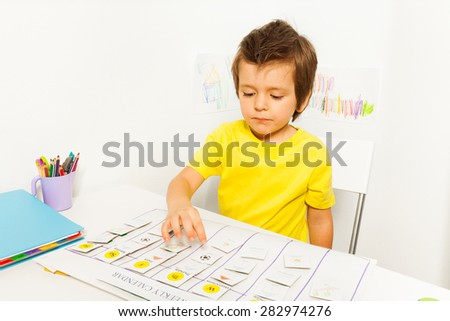 Boy plays in developing game pointing at calendar - stock photo