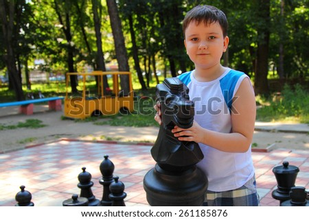 Boy plays in the big chess in a summer park - stock photo