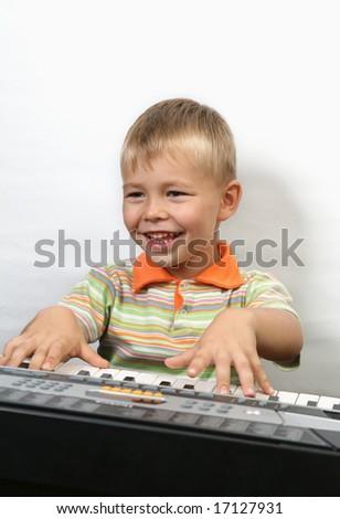 Boy plays piano - stock photo