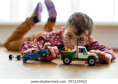 Boy plays with toy cars. Kid playing on the floor. Child's daytime fun. Happy to be at home. - stock photo