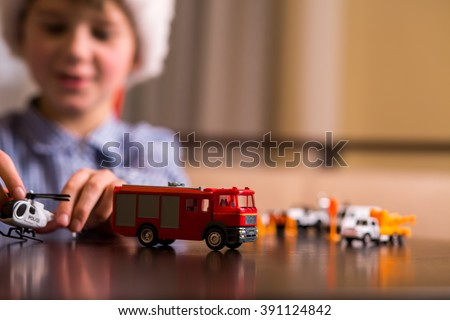 Boy plays with toy helicopter. Kid with toy police helicopter. Law enforcement and fire department. Always ready to act. - stock photo