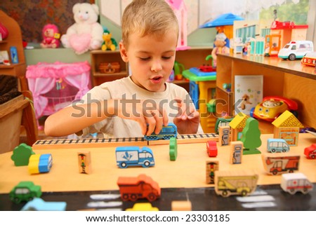Boy plays with toy  in playroom - stock photo
