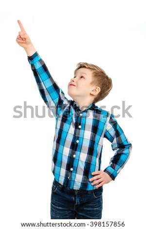 Boy pointing at something above him against a white background   - stock photo