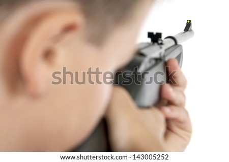 Boy pointing his airgun away from the camera. The focus is on the end of the barrel. Horizontal.