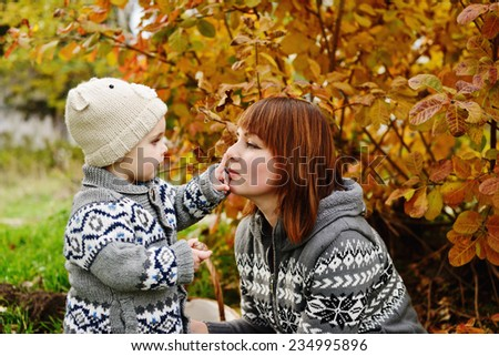 boy pointing mother's nose in fall time - stock photo