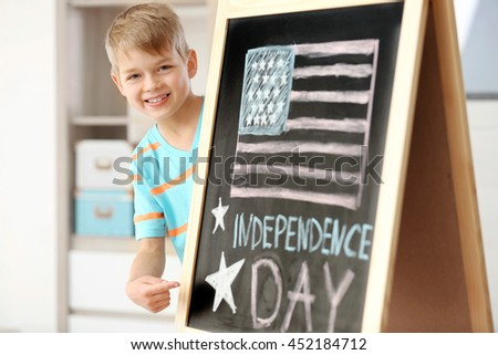 Boy pointing on chalk drawing of American flag on blackboard - stock photo