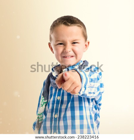 Boy pointing to the front over ocher background