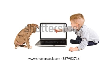 Boy points finger at the screen of laptop sitting with a puppy isolated on white background