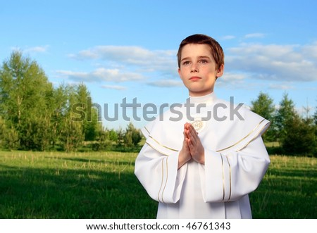 Boy portrait in his first holy communion, praying hands, clear conscience - stock photo
