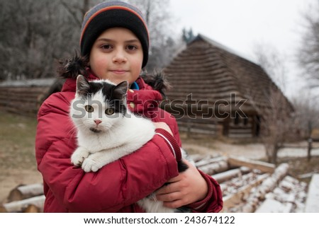 Boy portrait in warm clothes hugging cat, in the village. Copy space - stock photo