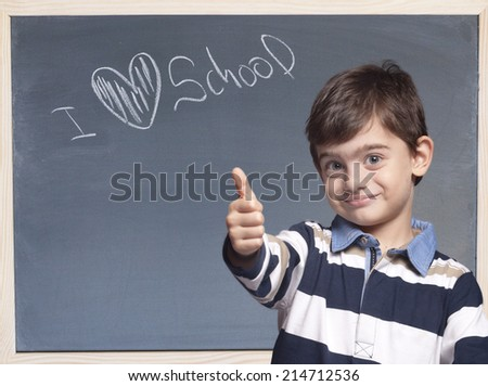 Boy posing in front of a blackboard with I Love School message