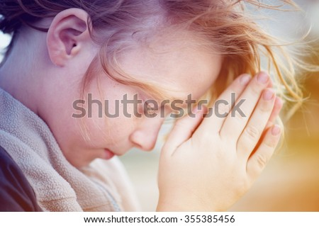 boy praying to God. - stock photo