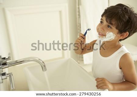 Boy Pretending To Shave In Bathroom Mirror - stock photo