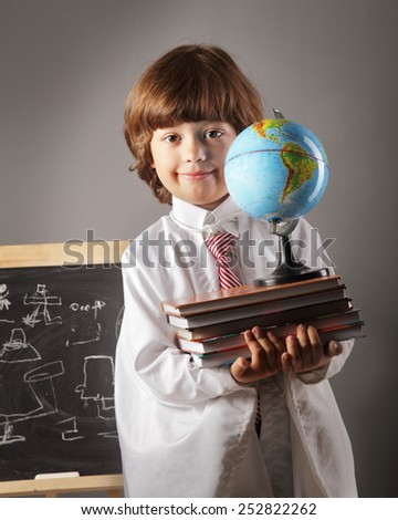 boy primary school students with books and globe at the blackboard - stock photo