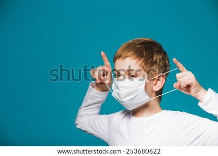 Boy putting on protection mask - stock photo