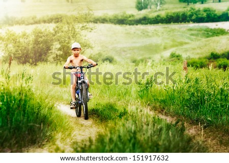 Boy racing on bike through green park - stock photo