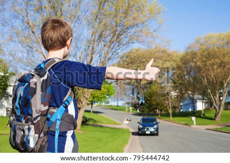 Boy raising his hand for stop the car. Autostop