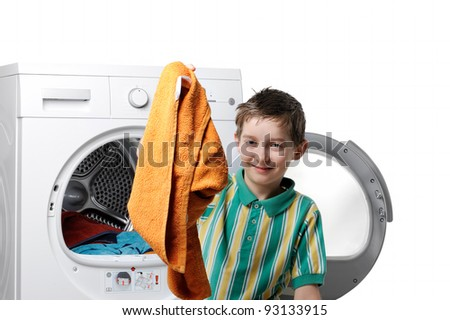 Boy reaching for the washed things out of the washing machine - stock photo