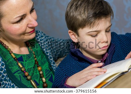 boy reading a book together with his mother